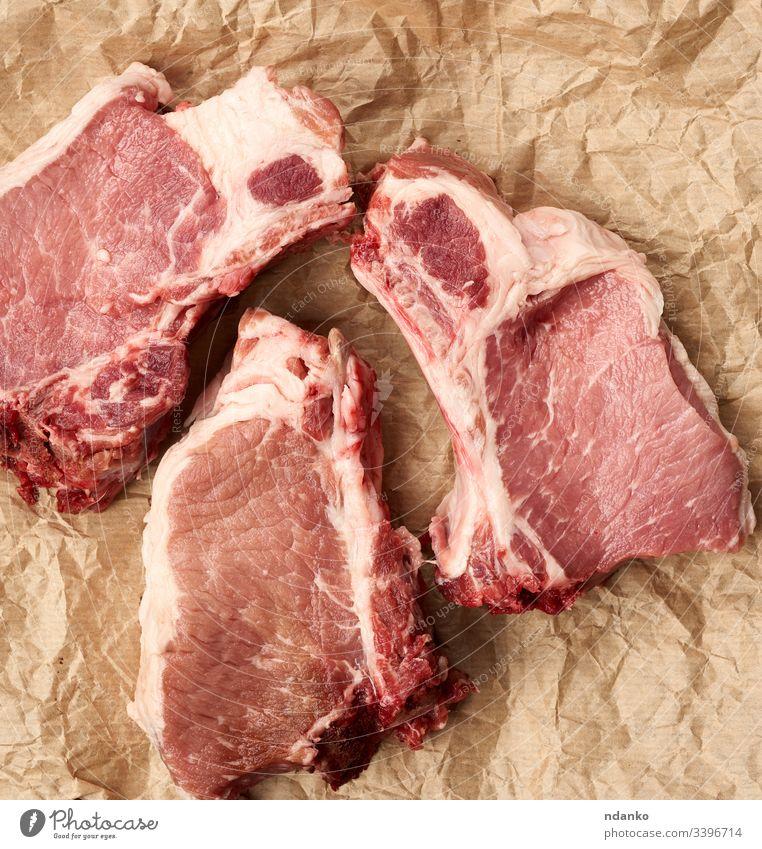 rohe saftige Schweinefleischscheiben auf der Rippe, die Nahrung liegt auf braunem Pergamentpapier Barbecue grillen schwarz Holzplatte Knochen hacken Koch