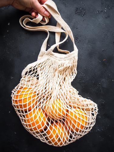 Hand mit einer wiederverwendbaren Einkaufstasche und frischen Orangen auf einem schwarzen Hintergrund orange einkaufstasche halten Gesunde Ernährung Frucht