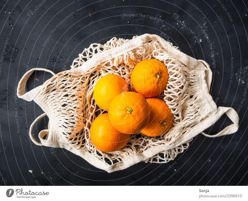Draufsicht auf frische Orangen in einer wiederverwendbaren Einkaufstasche auf einem schwarzen Hintergrund orange Frische einkaufstasche draufsicht orange Farbe