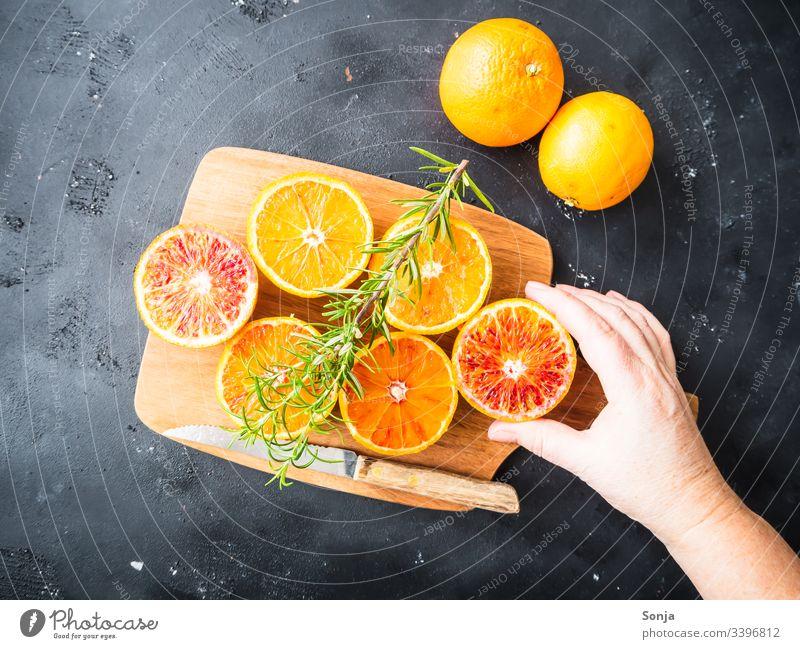 Hand mit frischen halbierten Orangen auf einem Holzschneidebrett auf einem schwarzen Hintergrund Frau orange holz messer rustikal draufsicht Frucht Arme