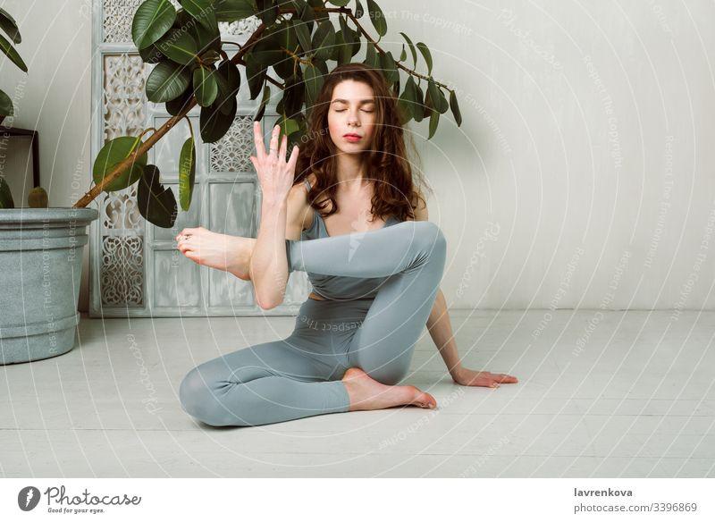 Junge Yogini beim Üben auf dem Boden in einem Raum mit weißen Wänden und Pflanzen Training aktiv Sport Übung dünn schlank Leggings brünett Windstille beweglich