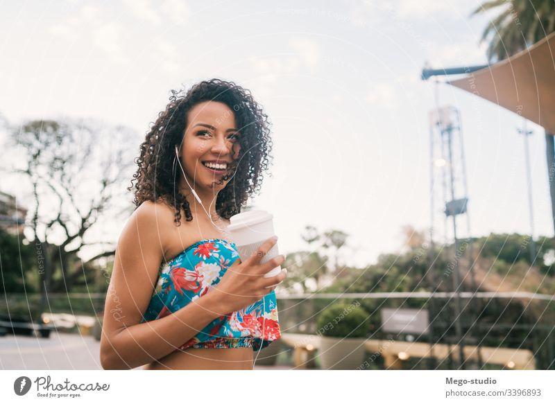 Afro-Frau, die Musik hört, während sie eine Tasse Kaffee hält. Kaffeetasse Kopfhörer Afro-Look Straße Ethnizität außerhalb stylisch zuhören Schönheit positiv