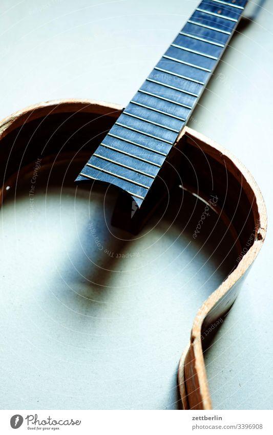 Gitarre again bruch bruchstelle decke gitarre hals innen instrument kaputt menschenleer musikinstrument saiteninstrument schaden teile textfreiraum unfall