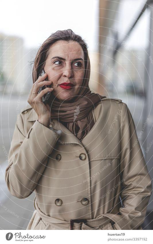 Arabische Frau mit Hidschab am Telefon Hijab attraktiv Koffer muslimisch muslimische Frau Handy arabisch Gepäck Reisen: islamisch Reisender Ausflug Fröhlichkeit