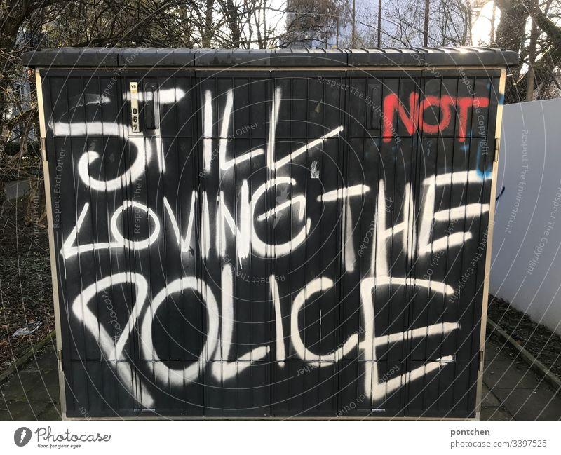 Graffiti auf einem Stromkasten. Englische r Text über die  Abneigung  gegenüber der  Polizei. Polizeigewalt abneigung graffiti stromkasten schwarz text satz