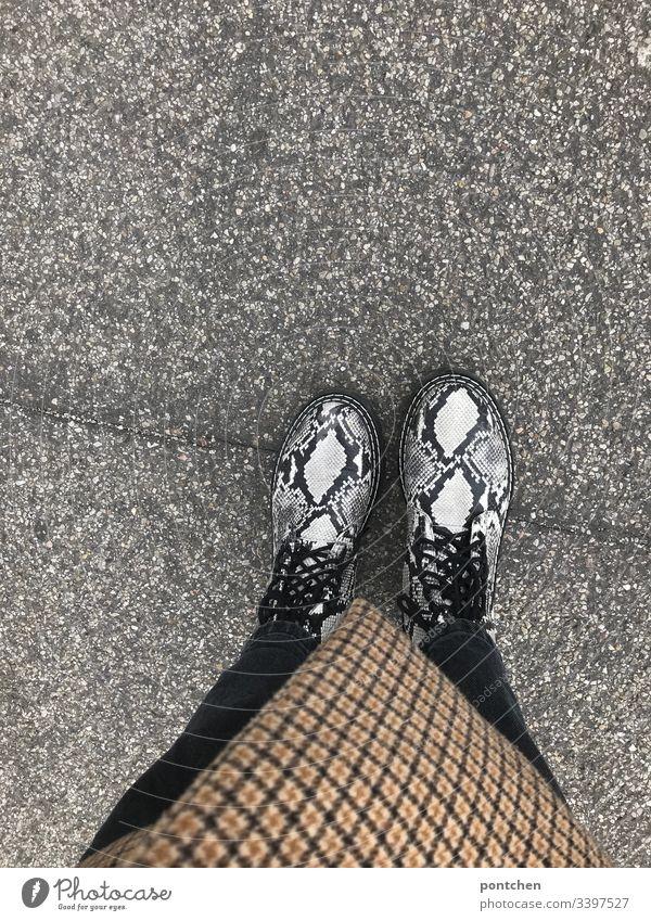 Blick von oben auf Unterkörper mit Schlangenlederschuhen stiefel muster manrepeller kariert karo mantel schnürsenkel mode trend hipster Asphalt straße teer Hose