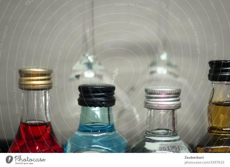 Vier Flaschen mit farbigen Spirituosen vor zwei Gläsern Flüssigkeiten Alkohol rot blau Getränk Glas trinken Minibar Hotel vier Nahaufnahme Freundschaft Reisen