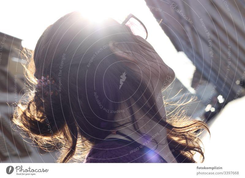Profil einer Frau im Gegenlicht, die in eine Gasse schaut Wegsehen beobachten blicken Stadtleben schauen warten draußen Denken Frisur himmelwärts Optimismus
