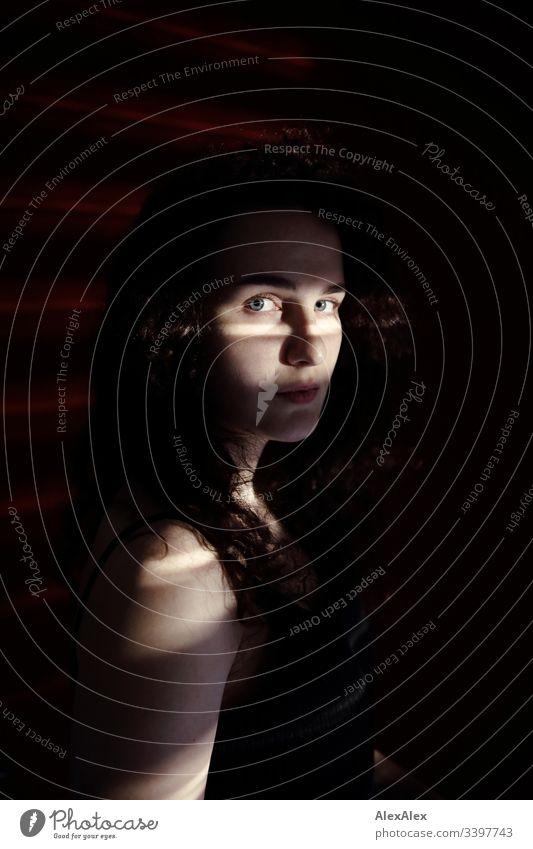 Lichtstreifen- und Schatten- Portrait einer jungen Frau vor roter Wand Schlank dunkelhaarig Stilrichtung elegant schön Leben Wohnung Raum Junge Frau Jugendliche
