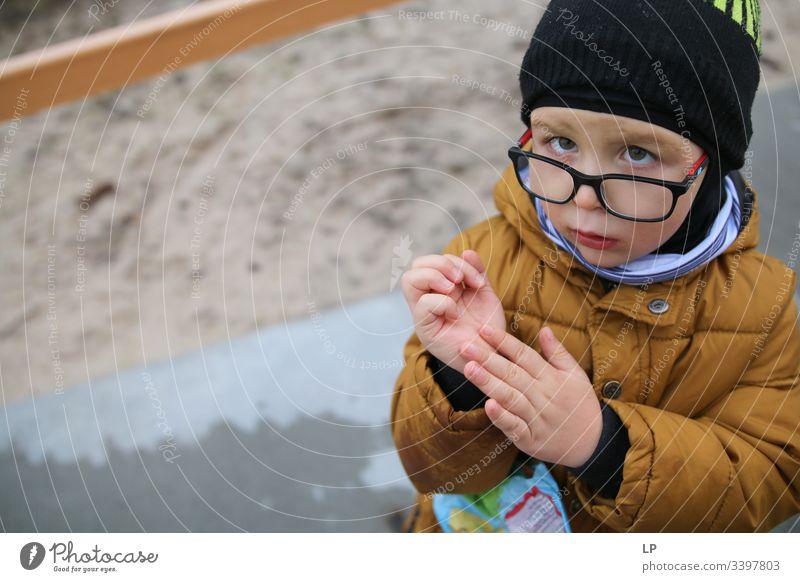 Junge, der in die Kamera schaut und seine Hand zeigt Blick in die Kamera beobachten neugierig nach unten Neugier Auge Kinderspiel Kindheitserinnerung