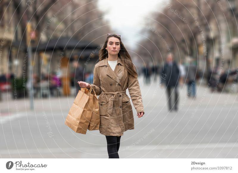 Junge Frau geht auf der Straße mit einer Einkaufstasche in der Hand Teenager gemischte Rasse Barcelona schön fallen asiatisch europa Glück Käufer Mode Spanien