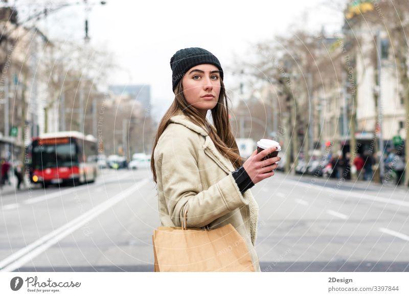 Porträt einer jungen europäischen Frau, die in einer Straße der Stadt spazieren geht, mit Kaffee zum Mitnehmen in der Hand modern allein schön Tasse attraktiv