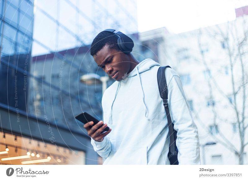 Junger schwarzer Mann steht auf der Straße und hört Musik über Kopfhörer Technik & Technologie Lifestyle männlich Freizeitkleidung trendy Glück Afrikanisch
