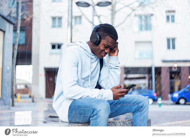 Junger schwarzer Mann sitzt auf einer Bank und hört Musik über Kopfhörer Technik & Technologie Lifestyle männlich Freizeitkleidung trendy Glück Afrikanisch