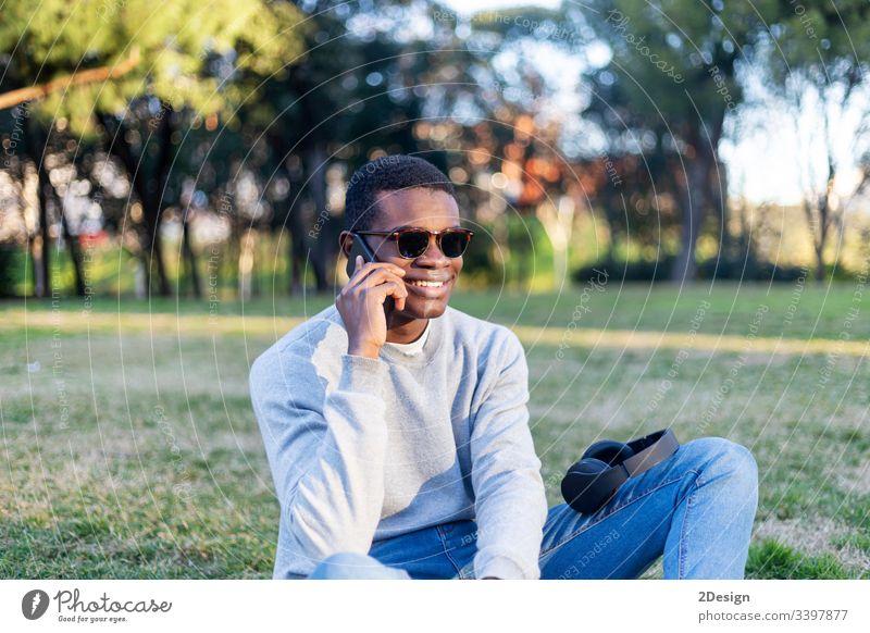 Modischer schwarzer Mann mit Sonnenbrille, der im Freien sitzt und seinen Nachrichten-Feed oder seine Nachrichten über soziale Netzwerke per Handy abruft