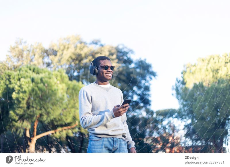 Afro-Jugendlicher, der ein Mobiltelefon benutzt. Stil Technik & Technologie 1 Lifestyle benutzend Einstellung männlich schwarz Straße Handy Freizeitkleidung