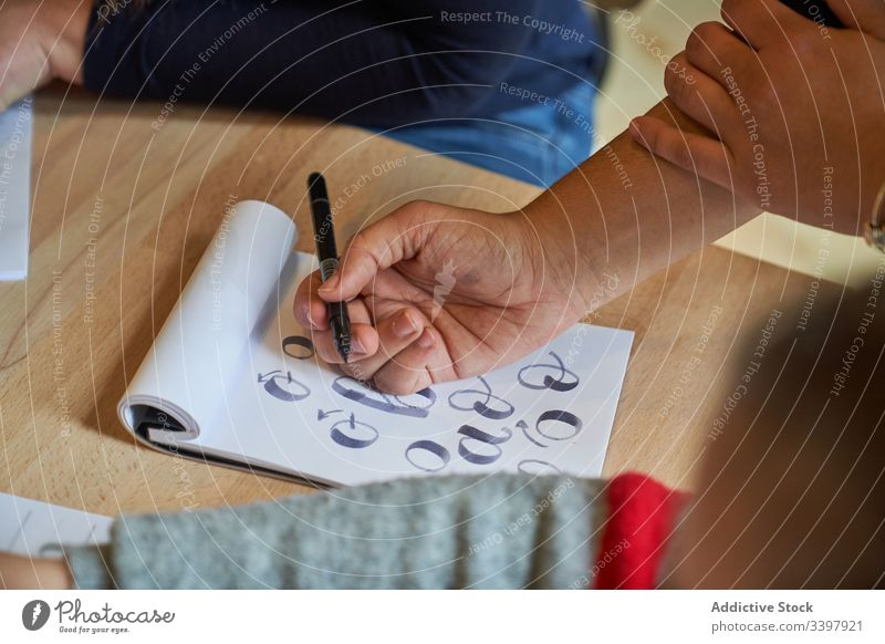 Gesichtslose Frau lernt Schriftzug bei Tisch Beschriftung zeichnen Papier Handschrift Beruf Schreibtisch Arbeitsplatz Kunst kreativ Handwerk graphisch Bildung