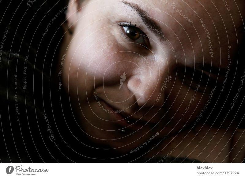 Portrait einer jungen Frau mit Lippenpiercing und Sommersprossen Blick nach vorn Porträt Zentralperspektive Schwache Tiefenschärfe Tag Nahaufnahme Innenaufnahme
