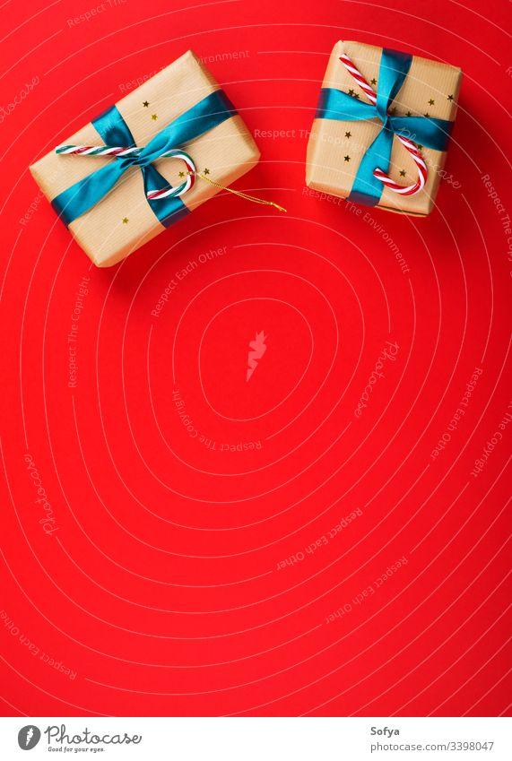 Geschenkverpackung mit grüner Schleife und Zuckerstangen auf rotem, fettem Hintergrund Weihnachten Neujahr präsentieren Feiertag flache Verlegung festlich