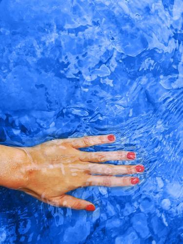 Klassische blaue Farbe des Jahres 2020. Weibliche Hand im Wasser klassisch Frau Spa Harmonie rot Maniküre Wellness Nägel Nagellack Urlaub Hintergrund