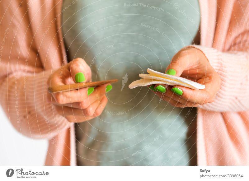Frau hält wiederverwendbare Wattepads und Holzkamm keine Verschwendung Baumwolle Polster Kamm rosa gesichtslos Hände Beteiligung Person tragend Pastell Kleidung