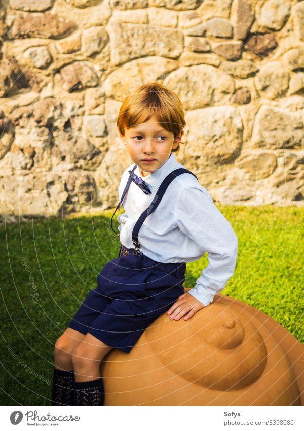 Kleiner eleganter Ringträger bei Gartenhochzeit Junge Hochzeit Junior striegeln Kind Blumenstrauß Sommer Porträt geblümt Mode Roséwein Natur Gesicht Sonne Glück
