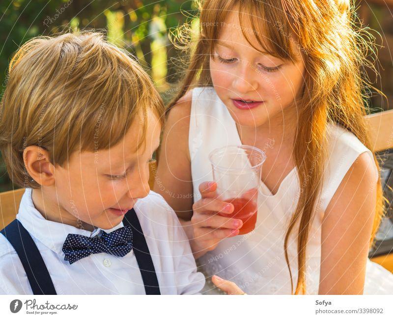 Elegante Kinder entspannen sich bei einer Hochzeit Mädchen Junge Glück herumhängen Pause anhaben elegant Kleidung Ringträger Sommer Geschwister spielen Natur