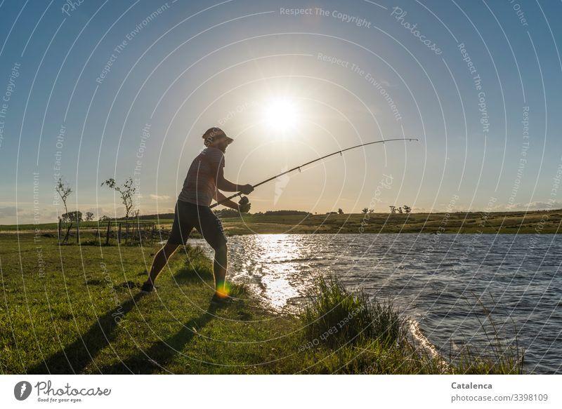 Junger Mann angelt am See, die Sonne steht tief, der Wind hat sich gelegt, die Fische sollten anbeißen Natur Umwelt Flora Pflanze Wiese Gras Wasser Gewässer