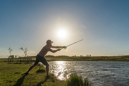 Junger Mann wirft am Seeufer eine Angel aus, die Sonne scheint, das Wasser glänzt Angeln Fisch Fischer Angelrute Farbfoto Küste Lebensmittel Angler