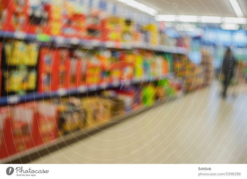 Verschwommene, bunte, volle Regale im Supermarkt und Kunde im Hintergrund Unschärfe Käufer Konsum Verbraucher bunt gemischt unscharf Neon-Beleuchtung