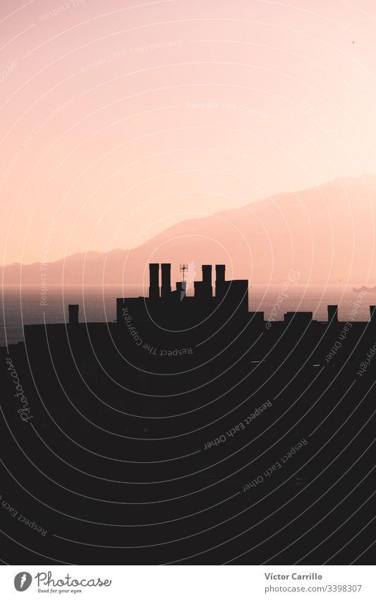Ein rosa Sonnenuntergang mit der Skyline der Gebäude Küste Berge u. Gebirge