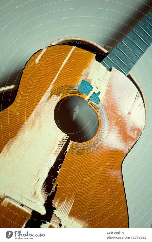 Kaputte Gitarre bruch bruchstelle decke gitarre hals innen instrument kaputt menschenleer musikinstrument saiteninstrument schaden teile textfreiraum unfall