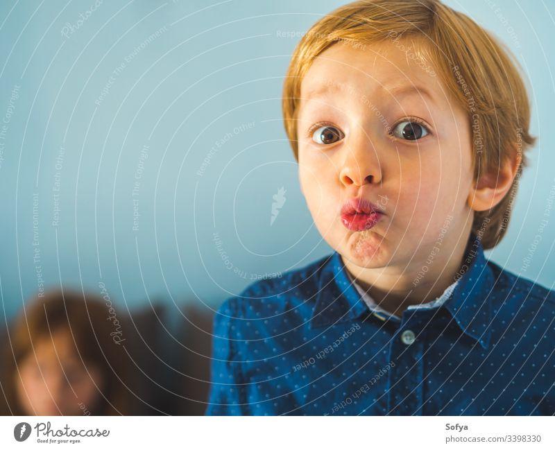 Kleiner blonder Junge mit komischem Gesichtsausdruck. Nahaufnahme-Portrait Kind wenig lustig Spaß Ausdruck Kaukasier Hemd blau Mode Auge Aussehen lebhaft Person