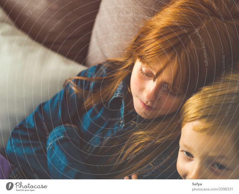 Zwei blonde kleine Kinder in Blau auf grauem Sofa Lächeln Gesicht Familie Geschwister Bruder Schwester Rotschopf wenig lustig süß Angebot Zusammensein