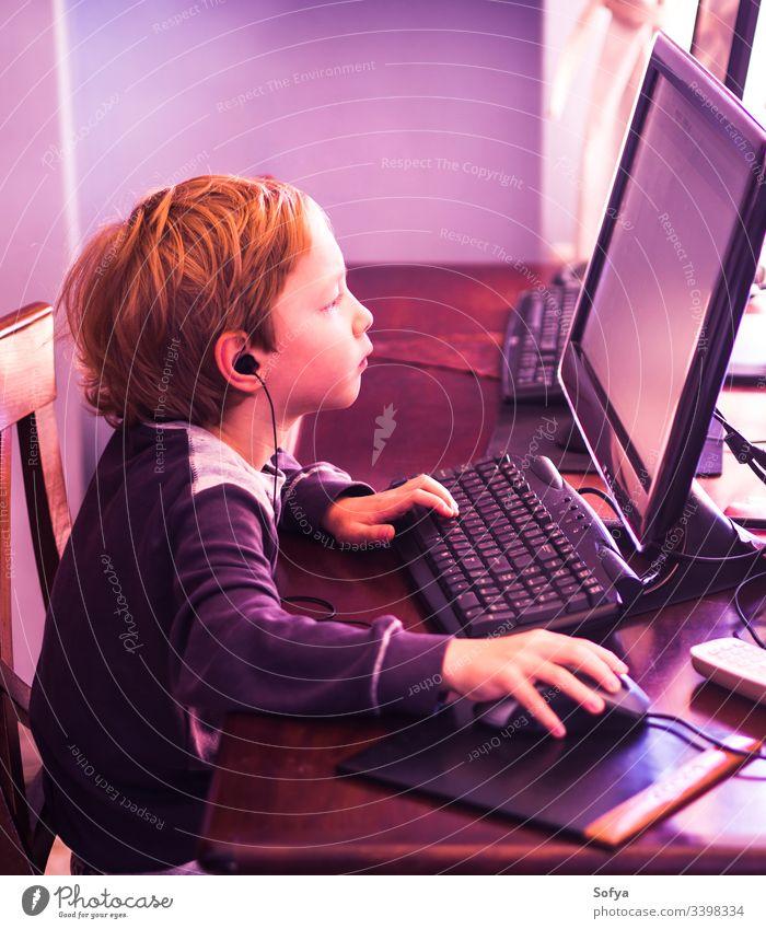 Süßer kleiner Junge spielt konzentriert am PC. Violetter Ton Computer Kind Technik & Technologie spielen Internet Freizeit männlich Person Lifestyle wenig Musik