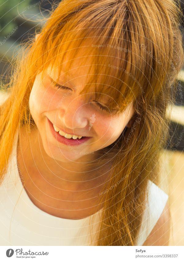 Nahaufnahme eines süß lächelnden rothaarigen Mädchens mit geschlossenen Augen in einem weißen Kleid im Sommer. wenig Kind Lächeln Porträt Rotschopf Glück