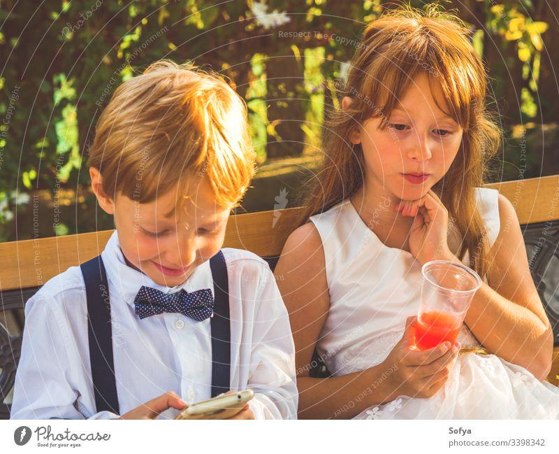 Ringträger und Blumenmädchen entspannen sich bei der Hochzeit Kinder Mädchen Technik & Technologie benutzend Smartphone Junge Glück Mobile Telefon herumhängen