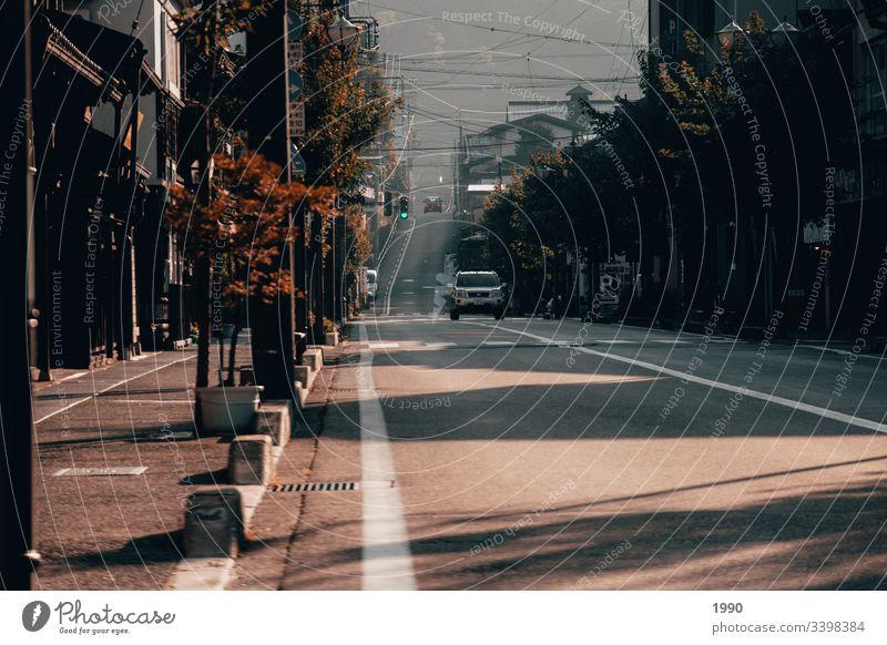 Morgendliche Fahrt bei Sonnenaufgang Straße Laufwerk Schatten Zebrastreifen bergauf Bergkuppe urban Landleben Landschaft Morgennebel Morgendlicher Spaziergang