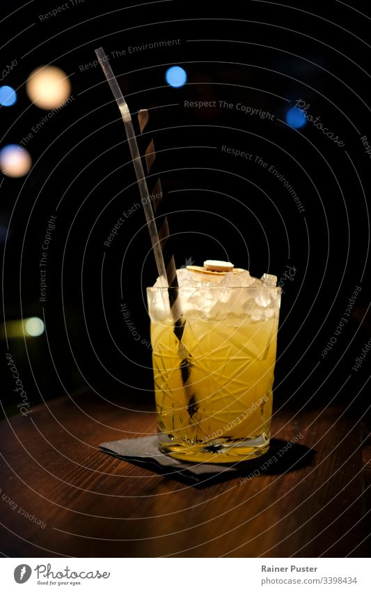 Köstlicher Cocktail mit zerstoßenem Eis in einer Cocktailbar mit Bokeh-Licht im Hintergrund Bar lecker geschmackvoll Nachtleben dunkel schwarz orange hölzern
