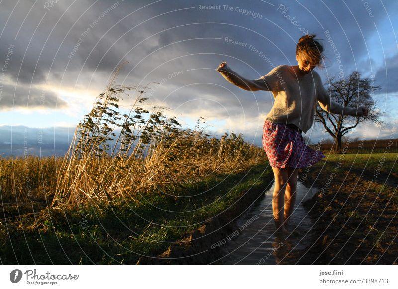 Frau steht in Pfütze im Feld Junge Frau Rock feminin Tag Wiese Acker Wolken Gewitterwolken windig Natur Landschaft Barfuß düster Sonnenlicht Ganzkörperaufnahme