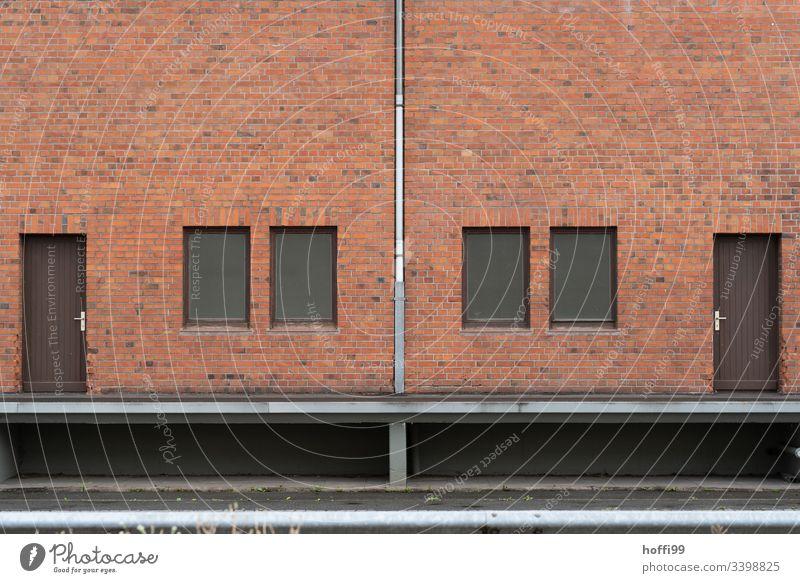 Symmetrische Rotklinker Fassade mit Fallrohr, Türen und Fenstern Klinkerfassade klinkerwand rotklinker Symmetrie Jalousie geschlossen Lagerhalle Lagerhaus Hafen
