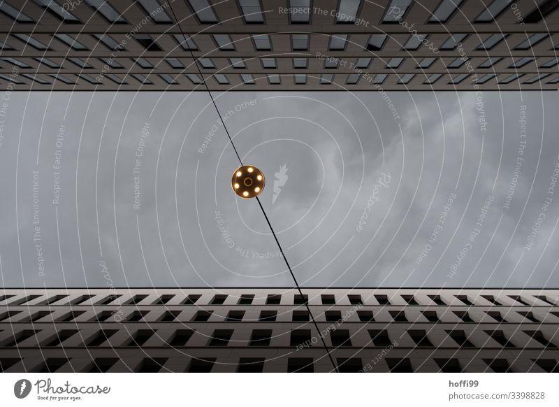 Blick nach oben auf eine Beleuchtung zwischen zwei Hochhäusern gegen grauen Himmel Froschperspektive Lampe Straßenbeleuchtung Hochaus hochhausschluchten
