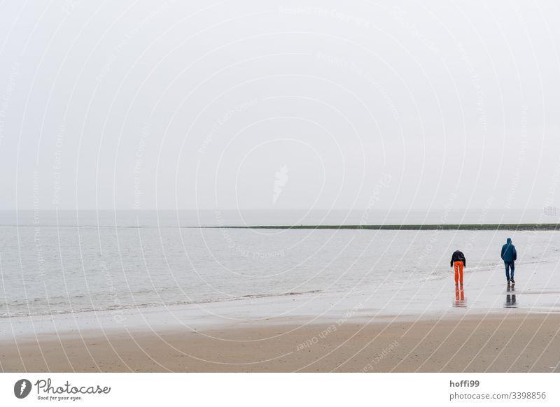 Pärchen geht im Winter bei Nebel am Strand spazieren Paar rote Hose Nordseeküste Wattenmeer Horizont Küste Insel Ferien & Urlaub & Reisen Sandstrand