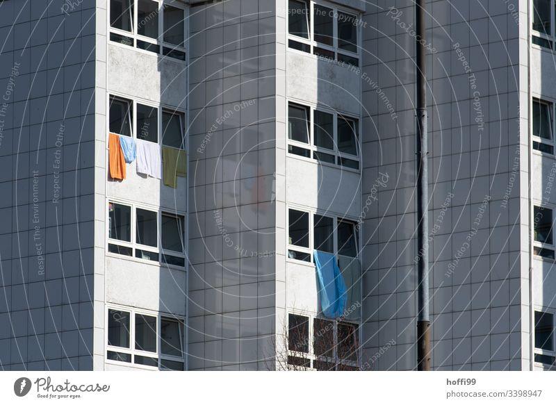Laken und Handtücher hängen aus dem Fenster eines Wohnblocks - Waschtag Hochhaus Bettlaken Handtuch Fassade Wand Mauer Armut Decke Enttäuschung Einsamkeit