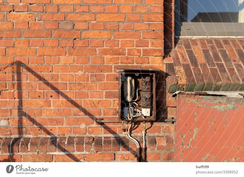 Telefon - alte Sprechstelle an rote Backsteinmauer Telekommunikation Anschluss Telefonhörer Kabel sprechen retro Wählscheibe Büro Kontakt altmodisch