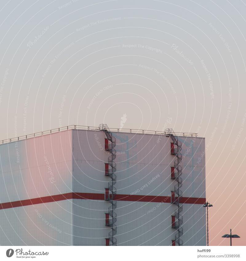 Lagerhalle mit Wendeltreppe bei Sonnenaufgang Fassade Dach rot Industrieanlage Lagerhaus Treppe Lampe Straßenbeleuchtung modern Morgen Morgendämmerung Fluchtweg