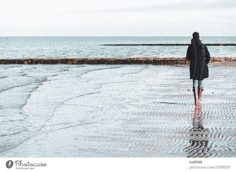 Frau mit rot gestreiften Gummistiefeln geht im Winter allein am Strand spazieren rote Gummistiefel Beine Stiefel Nordseeküste Wattenmeer Landschaft Umwelt