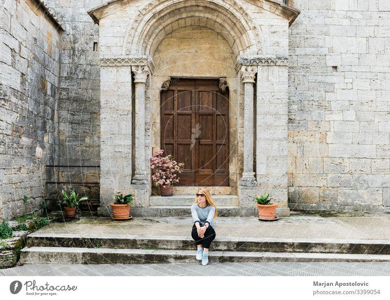 Junge Reisende sitzt auf den Stufen einer mittelalterlichen Kirche in der Toskana, Italien Erwachsener antik Antiquität Architektur Gebäude lässig katholisch