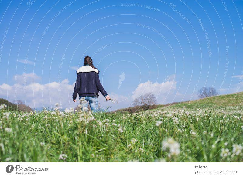 Rückansicht einer brünetten hispanischen Frau in Freizeitkleidung, die auf dem Feld geht Blume grün Rücken Freiheit Frühling 1 Ansicht Natur allein Sommer
