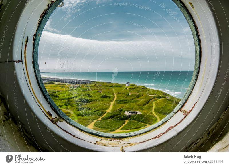 Blick aus dem runden Fenster eines Leuchtturms auf die Küste Dänemarks fenster Flugzeug Himmel Spiegel flieger Aussicht Weitblick Wolken Landschaft Bullauge
